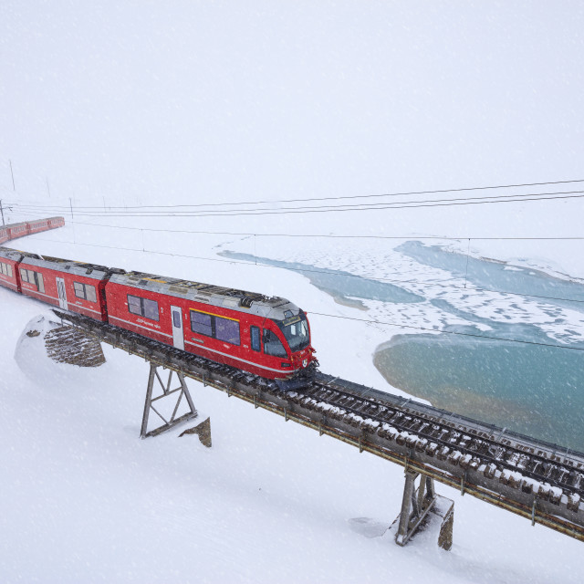 """Bernina Express train at Bernina Pass under a snowfall, canton of..."" stock image"