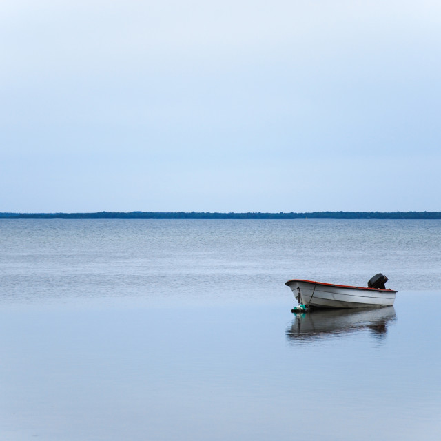 """Alone small boat in calm water"" stock image"