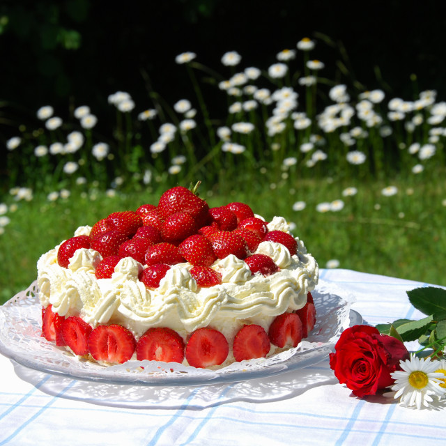"""Garden table with a strawberry cake and summer flowers"" stock image"