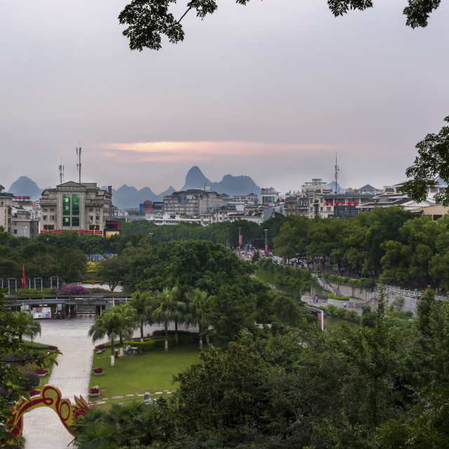 """""""Guilin, China - July 31, 2010: View of the skyline of the city of Guilin with the famous limestone peaks on the background at sunset, in China, Asia."""" stock image"""