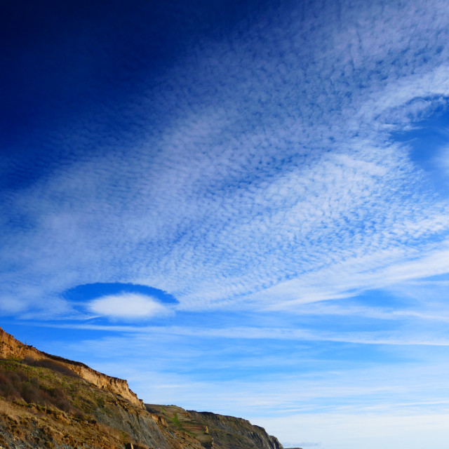 """Fallstreak clouds from Eype beach, Dorset"" stock image"