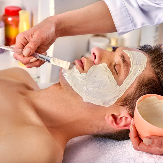 """Mud facial mask of woman in spa salon. Face massage."" stock image"