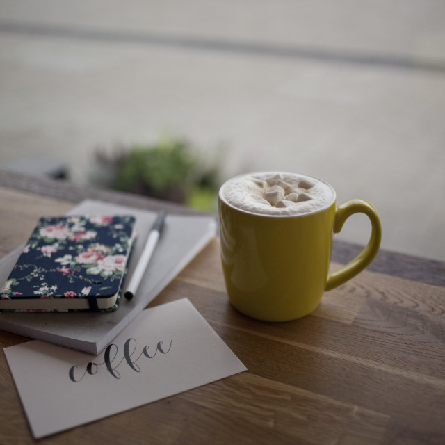 """Cup of coffee and notebooks near the window"" stock image"