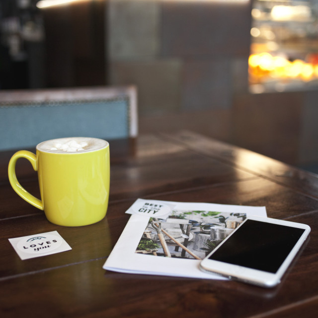 """Cup of coffee and smart phone on the wooden table"" stock image"