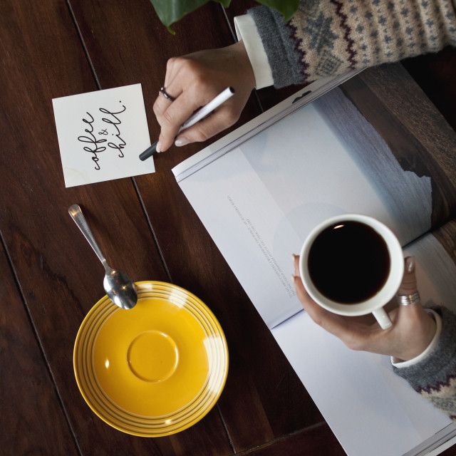 """Hands holding a pen and writing a note and drinking coffee"" stock image"