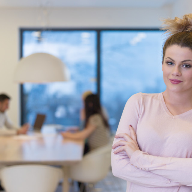"""""""Portrait of smiling casual businesswoman using tablet with coworkers..."""" stock image"""