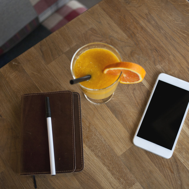 """Smart phone and orange juice on the wooden table"" stock image"
