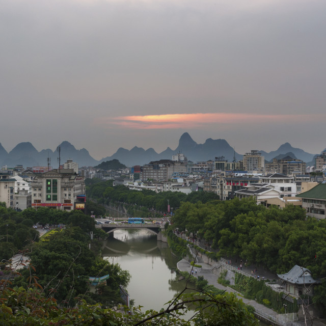 """Guilin, China - July 31, 2010: View of the skyline of the city of Guilin with the famous limestone peaks on the background at sunset, in China, Asia."" stock image"