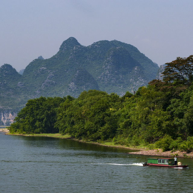 """Yangshuo, China - August 1, 2010: Small boal in the Li River with the tall limestone peaks in the background near Yangshuo in China, Asia."" stock image"