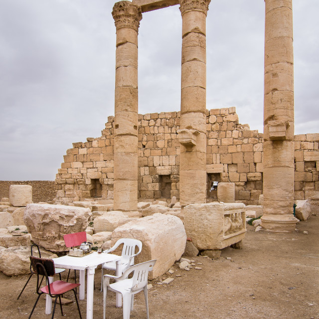 """""""Corinthian columns and fragments below, and a plastic table set for coffee, in the ancient Semitic city of Palmyra, Homs, Syria. Palmyra flourished in the Hellenistic period under the Seleucids and later as an independent city state of the Roman empire. I"""" stock image"""