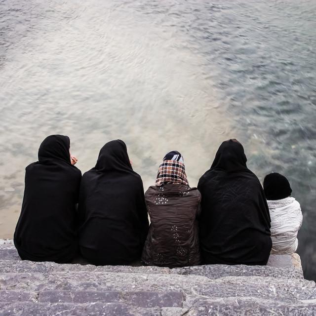 """""""Young women sat close to Zayandeh River at Khaju bridge. Isfahan, Iran"""" stock image"""