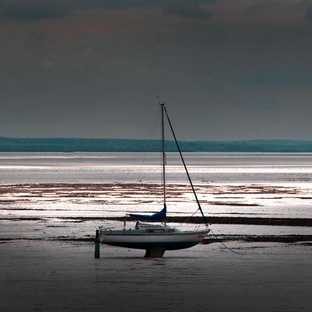 """Beached yacht on tidal estuary"" stock image"