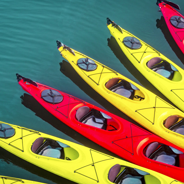 """kayak background with many kayaks on the surface of the ocean with red and yellow kayaks"" stock image"