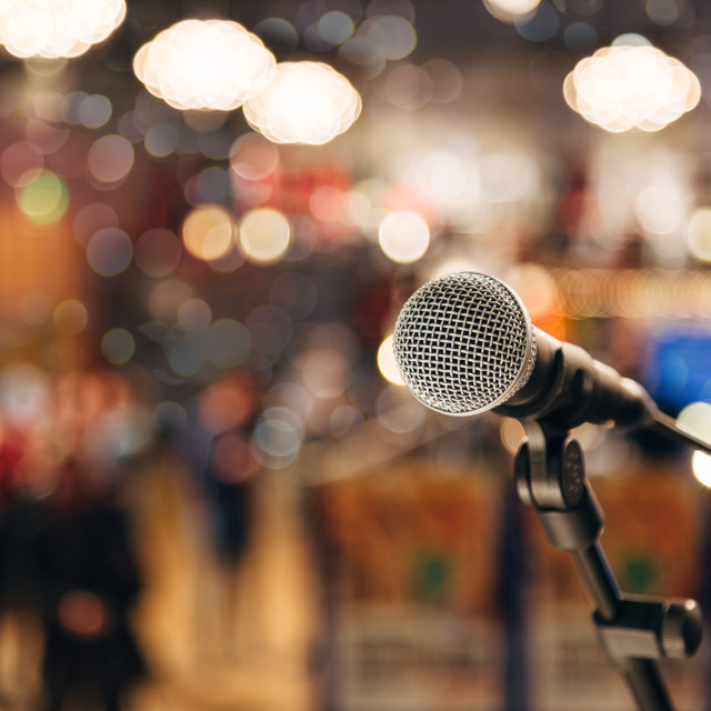 """Microphone on a stand ready for live music performance or karaoke night with soft bokeh lights and people silhouettes in the background."" stock image"