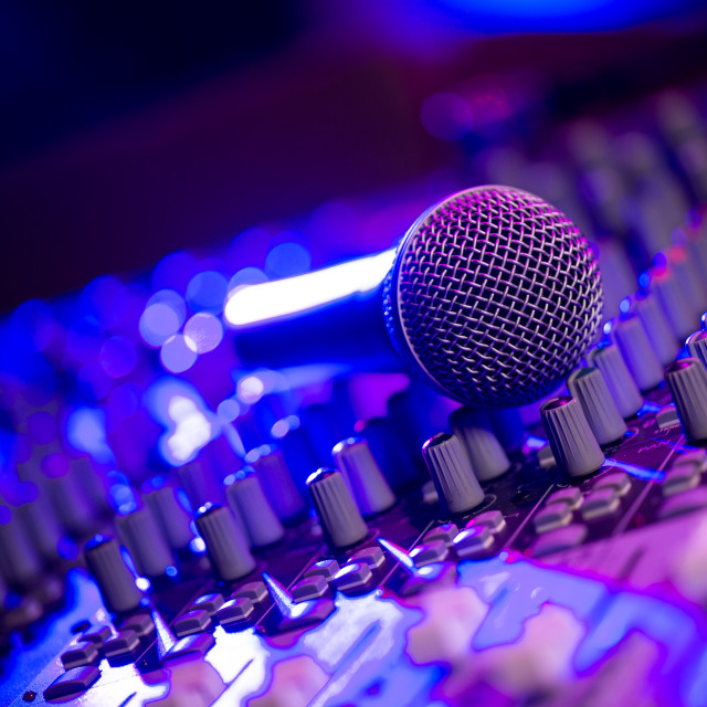 """""""Microphone and Headphones on dirty sound mixer panel"""" stock image"""