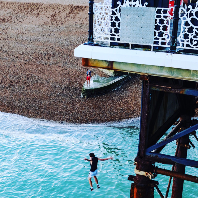 """""""Brighton pier man dives off to join friends swimming"""" stock image"""