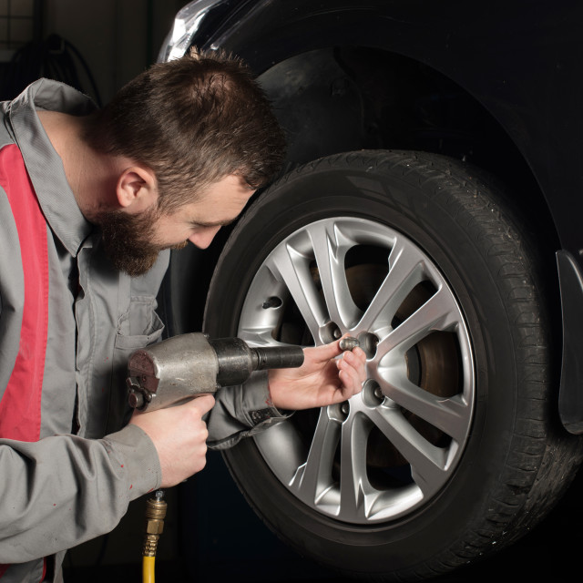 """mechanic preparing to change the tire"" stock image"