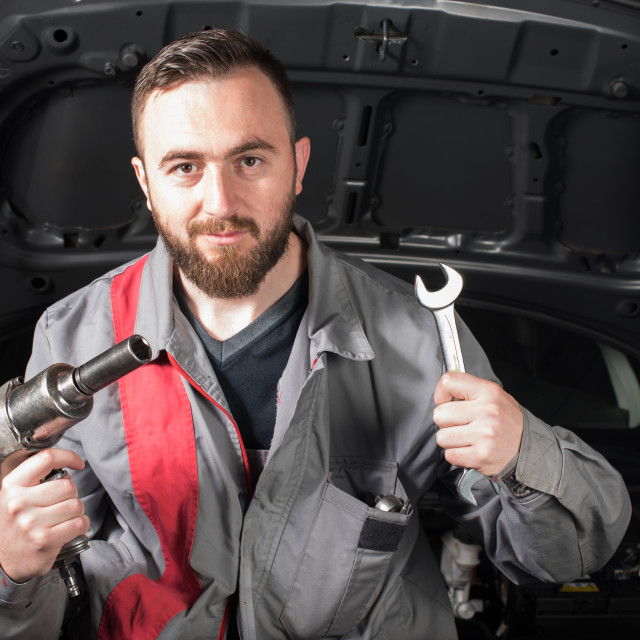 """mechanic with tire pistol and wrench in hands"" stock image"