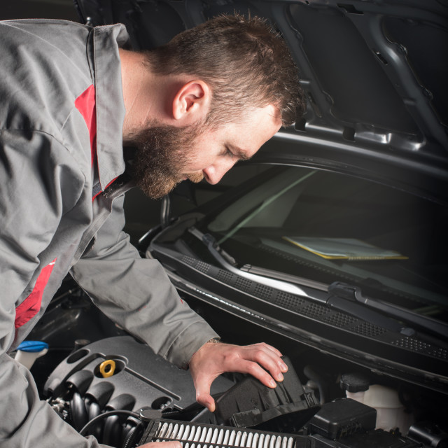 """mechanic changing the air filter on car"" stock image"