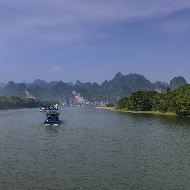 """""""Yangshuo, China - August 1, 2010: Passenger boats with tourists in the Li River with the tall limestone peaks in the background near Yangshuo in China, Asia."""" stock image"""