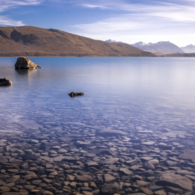 """Early Morning water's calm on the shores of Lake Tekapo, New Zealand"" stock image"