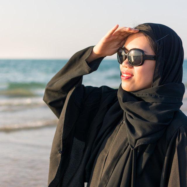 """Portrait of a woman in abaya on the beach"" stock image"