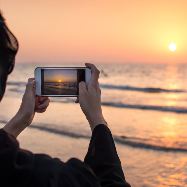 """Woman in hijab taking picture of a sunset"" stock image"
