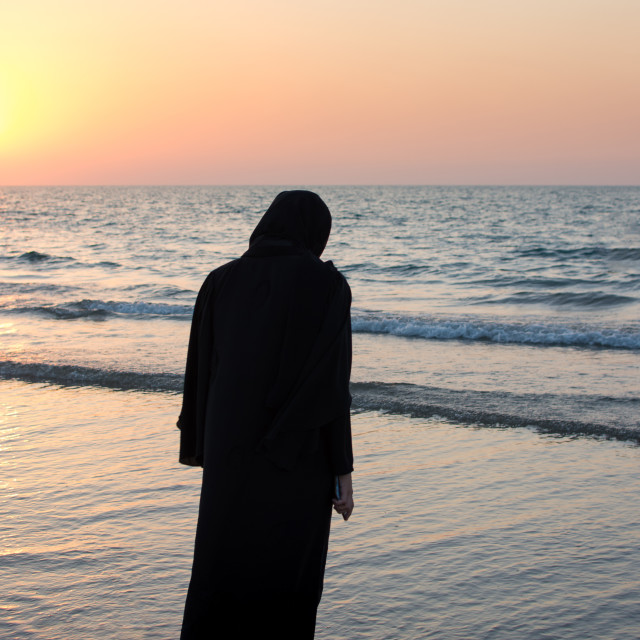 """Woman in hijab standing on the beach"" stock image"