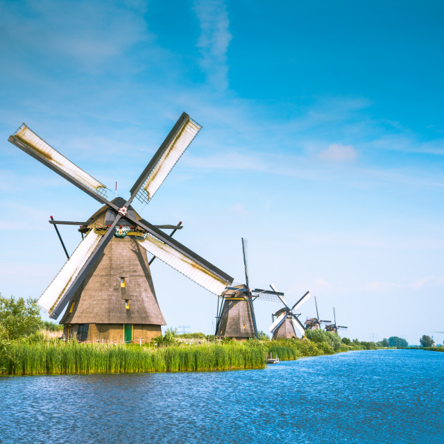 """""""Traditional village with dutch windmills and river at sunset, Holland, Netherlands."""" stock image"""