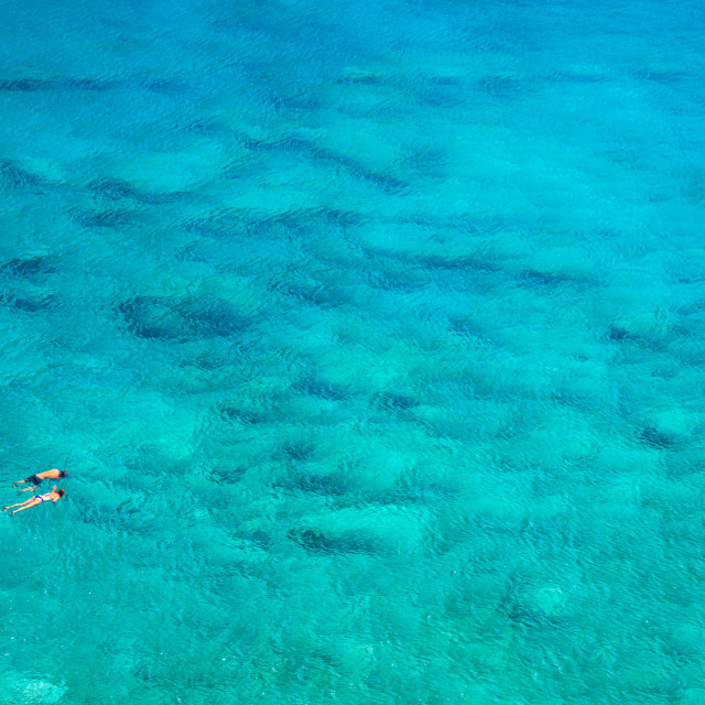 """Above view of couple snorkeling in turquoise sea water, Glyka Nera, Chania, Crete, Greece"" stock image"