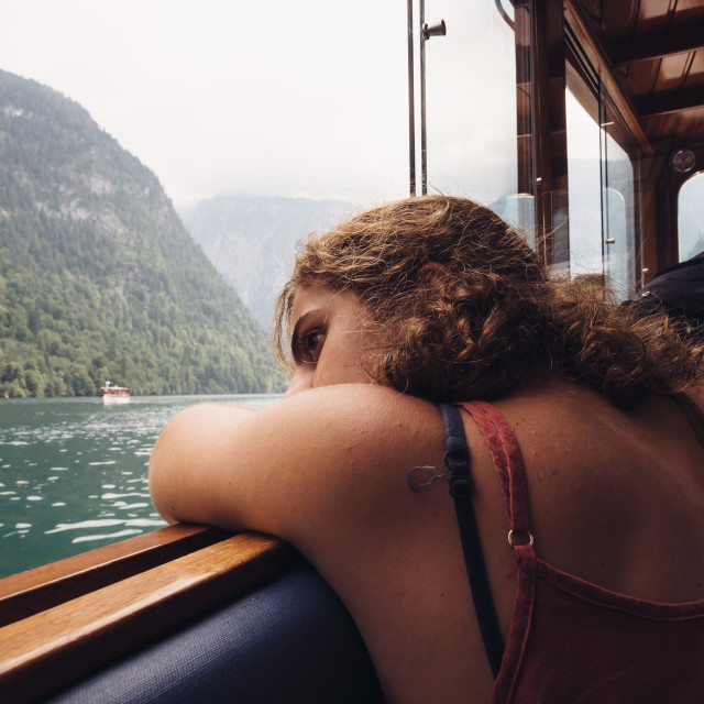 """""""Young woman sitting on the boat by beautiful lake."""" stock image"""