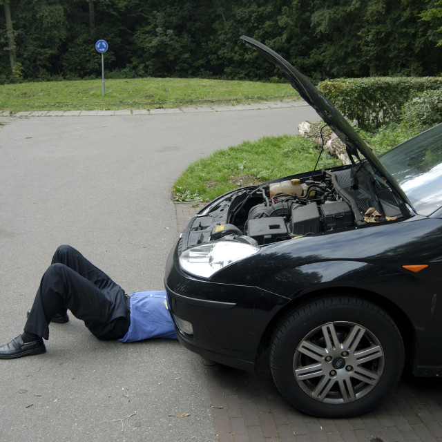 """Man repairing a car, bonnet up and feet sticking out form underneath."" stock image"