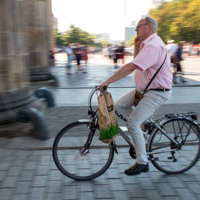 """Man on Bike with a phone"" stock image"