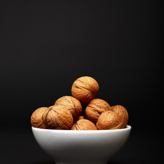 """""""Walnuts heaped in a bowl"""" stock image"""