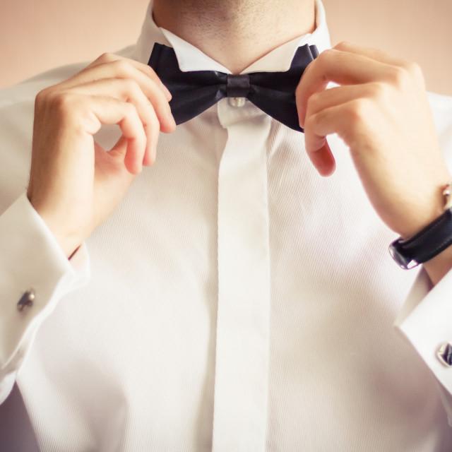 """Closeup of business man adjusting neck bow"" stock image"