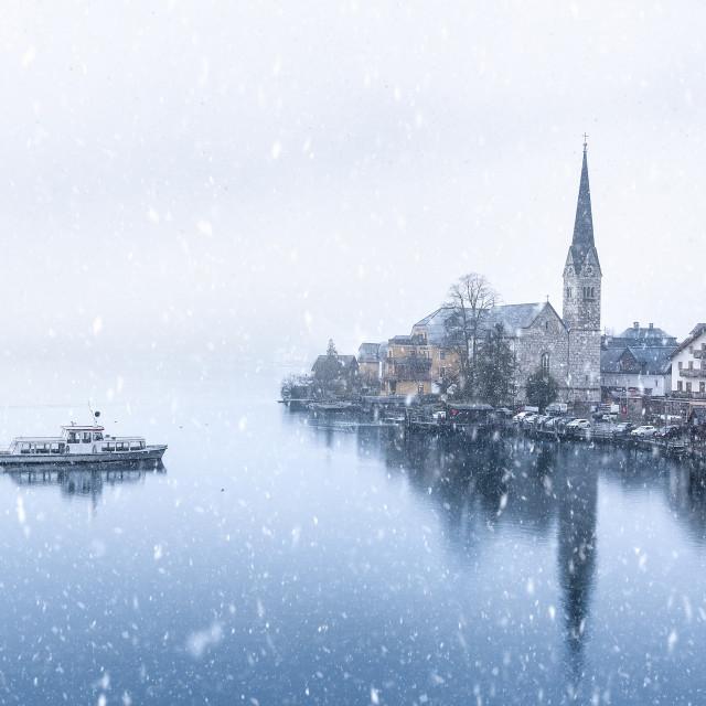 """Hallstatt town and a boat under snowfall"" stock image"