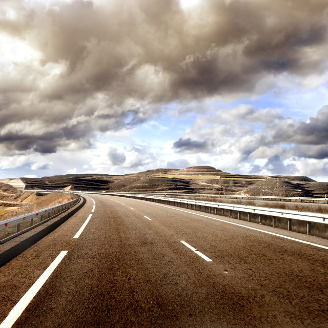 """Empty highway,mountain landscape and cloudy sky.Road and car tra"" stock image"