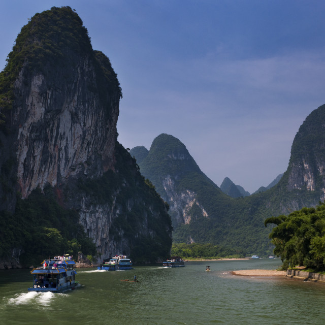 """Yangshuo, China - August 1, 2010: Passenger boats with tourists in the Li River with the tall limestone peaks in the background near Yangshuo in China, Asia."" stock image"
