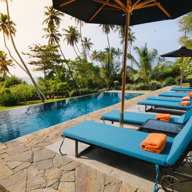 """""""Swimming pool and lounge chairs facing a garden and the sea in boutique hotel."""" stock image"""