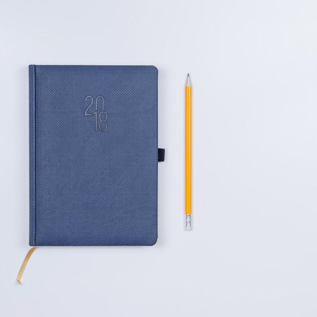 """""""Pretty diary with a pencil on the white table."""" stock image"""