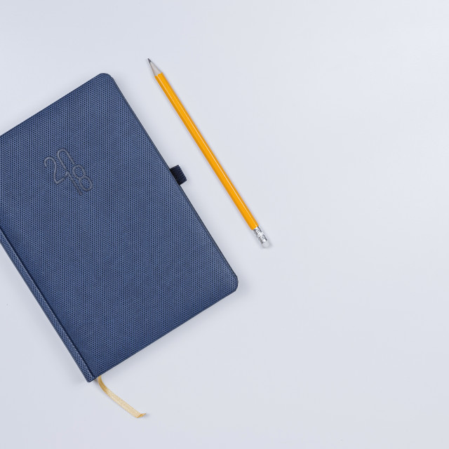 """Pretty diary with a pencil on the white table."" stock image"