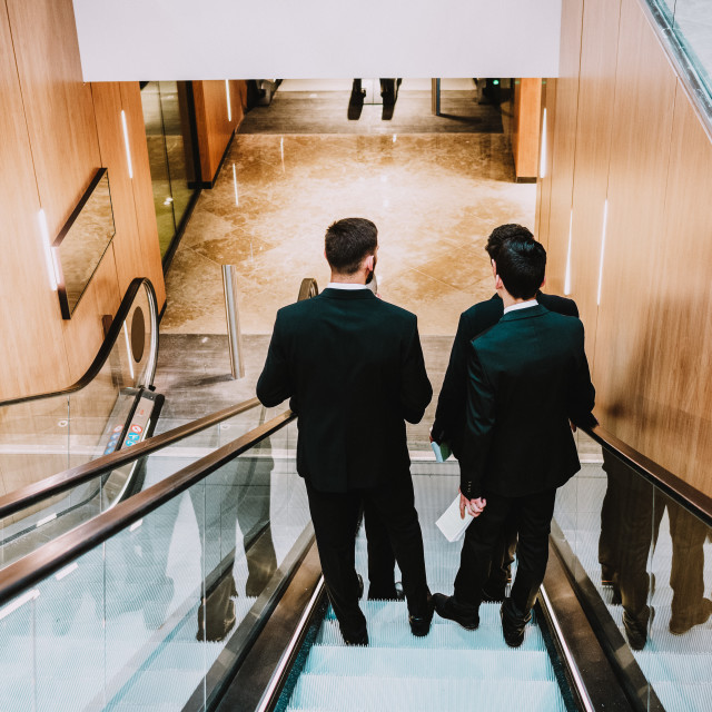 """""""4 men in suit in the shopping center or buisnes center."""" stock image"""