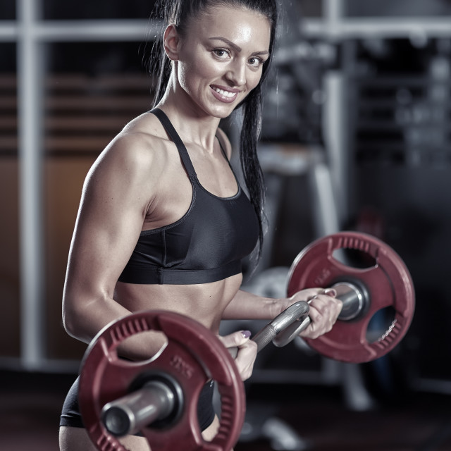 """Young woman doing biceps curl with barbell"" stock image"