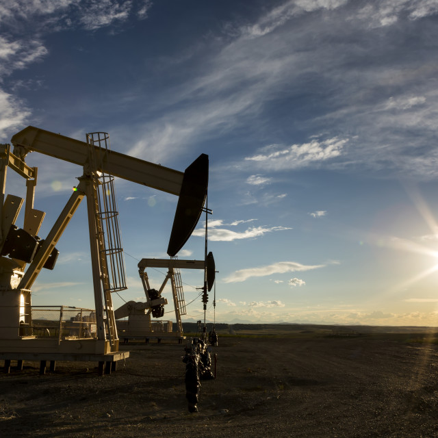 """A pumpjack backlit by the setting sun on the Alberta Prairies with blue sky..."" stock image"