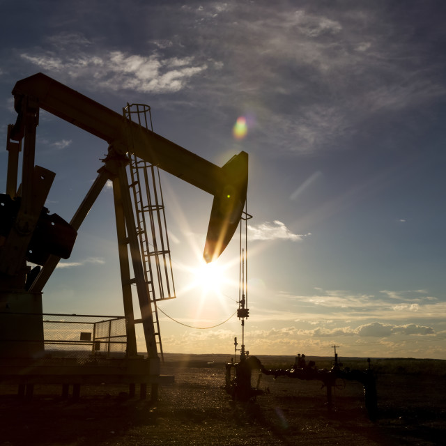 """""""Silhouette of a pumpjack backlit by the setting sun on the Alberta Prairies..."""" stock image"""