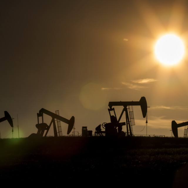 """Silhouette of numerous pumpjacks in a field with a glowing sun at sunset on..."" stock image"