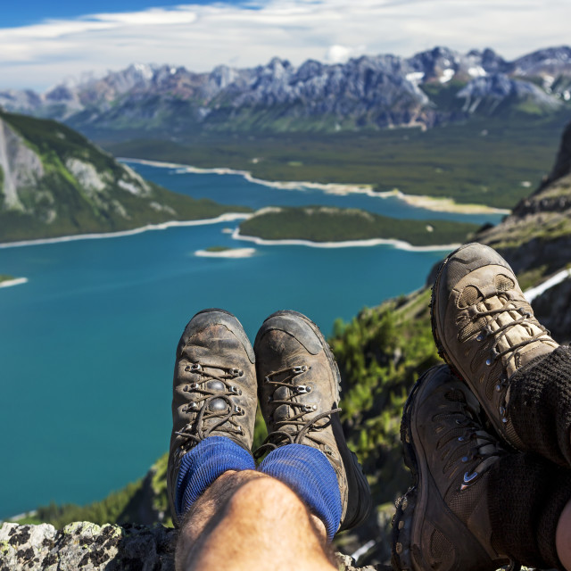 """""""Close-up of a couple's hiking boots over a cliff overlooking a colourful..."""" stock image"""