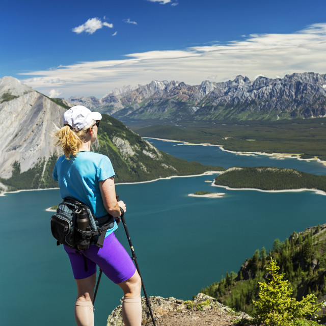 """Female hiker on ridge top overlooking a colourful alpine lake and mountain..."" stock image"