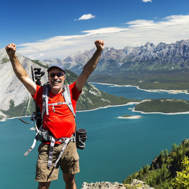 """Female hiker on ridge top with arms in the air, and a colourful alpine lake..."" stock image"