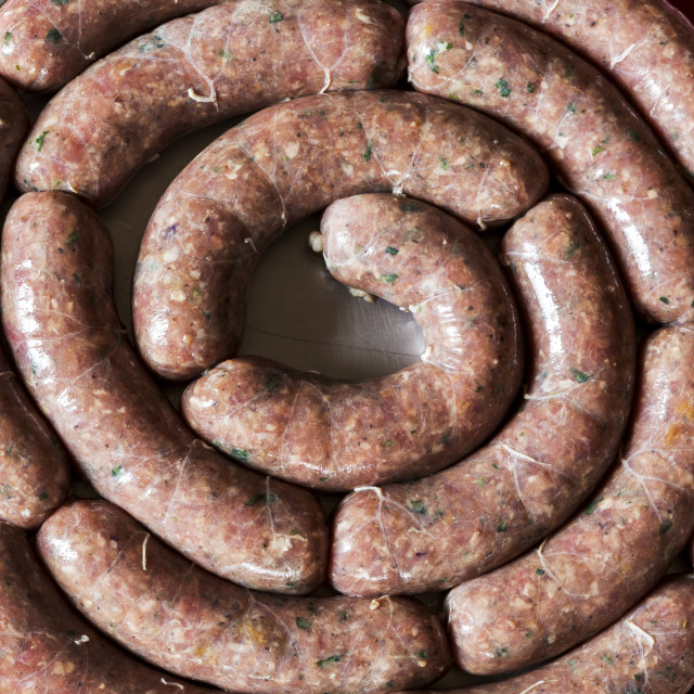 """Close-up of a circle of uncooked sausage links on a round cooking tray on a..."" stock image"